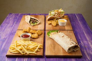 nuggets and french fries, Turkish shawarma, pita and Greek gyros with chocolate and kiwi on a table