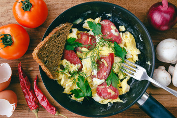 Fresh cooked scrambled eggs in pan with sausage and herbs. Bread, fork, vegetables on wooden board, top view.