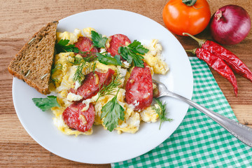 Fresh cooked scrambled eggs with sausage and herbs in white plate.Bread, napkin, fork, vegetables on wooden board.