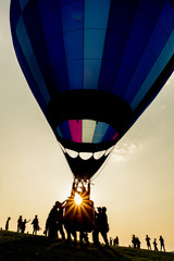 Silhouette of people with hot air balloon with colored envelope at sunset, backlit by sunlight photography