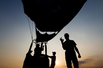 Silhouette of people with hot air balloon in the background at sunset, back-lit by sunlight photography