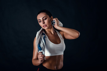 Attractive athletic young woman with perfect body wearing sportswear is posing with a towel against black background. Beautiful fitness girl relaxing after workout.