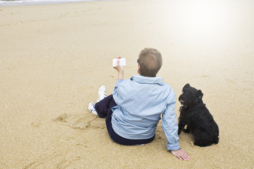 senior woman with dog and phone on the beach.