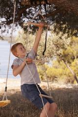 Croatia, Dalmatia, Boy climbing a rope ladder, portrait