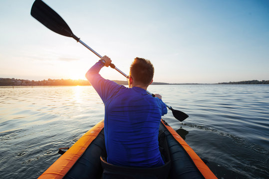 man floating on lake in a kayak at fantastic sunset.