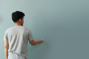 Man drawing gesture with white chalk on chalkboard or wall.