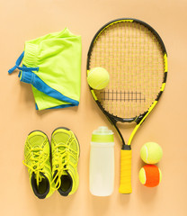 Tennis stuff on cream background. Sport, fitness, tennis, healthy lifestyle, sport stuff. Tennis racket, lime trainers, tennis ball, lime athletic shorts, sports bottle. Flat lay, top view.