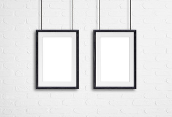 Wooden frames hanging on cords against white bricks wall. Gallery style, interior decor mock up