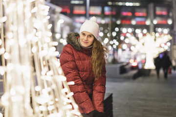 Young girl in winter clothes in the night city.