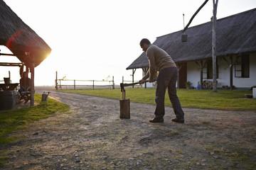 Man Splitting Log In Half, Woman In Background, Baranja, Croatia, Europe