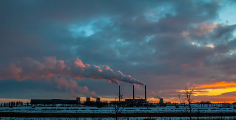 smoke out of the pipe at the factory, in winter, at sunset