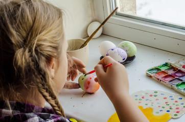Girl paints easter eggs
