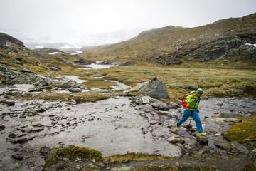 Hiker crossing mountain stream, Norway, Europe