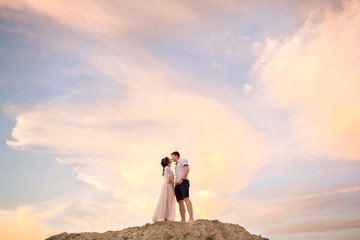 Happy couple kissing on sand mountain on sky background. Honeymoon concept