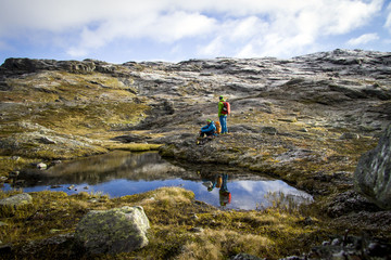Two hikers take a rest at mountain lake, Norway, Europe