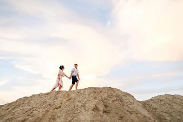Honeymoon. Young couple walking on sand mountain