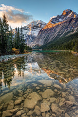 Mount Edith Cavell reflected in the calm river at sunrise in the rocky mountains of Jasper National Park, Alberta, Canada