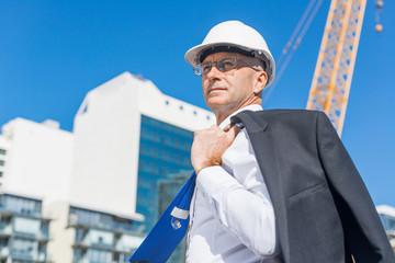 Senior elegant builder man in suit at construction site on sunny summer day