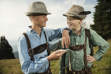 Germany, Bavaria, Two boys in traditional clothing using smart phone
