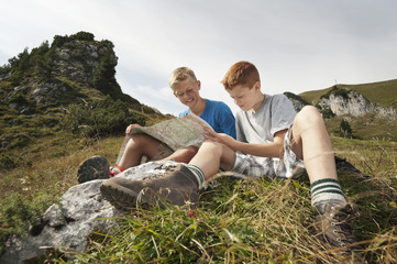 Germany, Bavaria, Two boys in mountains reading a map