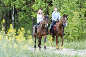 Photo sur cadre textile Equitation Young couple enjoying horseback riding.
