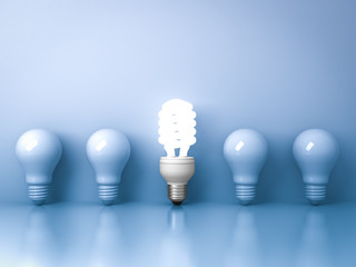 Energy saving light bulb one glowing compact fluorescent lightbulb standing out from unlit incandescent bulbs on blue background  individuality and different creative idea concepts 3D rendering