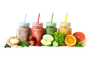 Four different smoothies in a glass jars and ingredients.