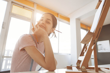 portrait of a happy young woman artist in front of a desk easel