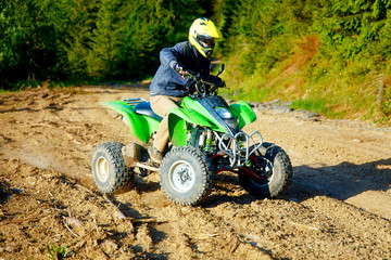 Poster Motorise racer with yellow helmet on green quad enjoying his ride outdoors.