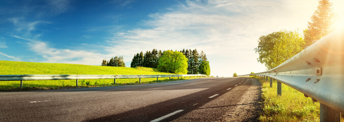 asphalt road panorama in countryside on sunny spring evening Wall mural