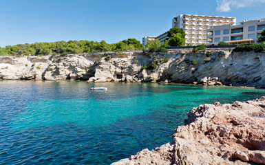Beautiful turquoise bay at Ibiza. Hotel on the beach. Luxury rest at Balearic Islands. Beautiful place for diving. Holidays in the Mediterranean.