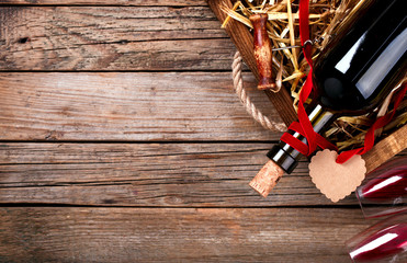 Bottle of red Wine Two Glass of Glass in a Wooden Box on the old Background. Concept for the Holiday Valentine's Day.Toned image.Vintage style.  top view. Copy space.selective focus.