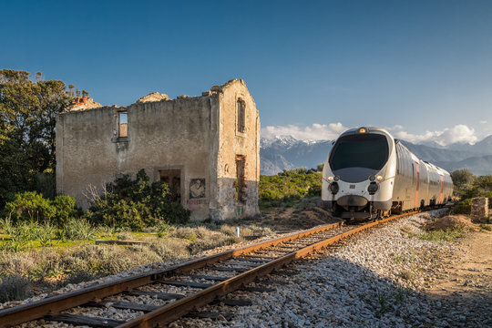 Train passing derelict station at Lumio in Corsica