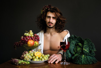 half naked curly guy sitting at a table with fruits and wine photo