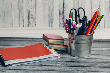 Stationery in a stand and notepads on the table