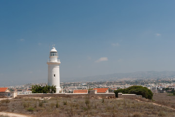 White  lighthouse and road on deserted seashore near Paphos city, Cyprus
