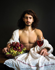 photo half naked curly guy sitting at a table with fruits and wine