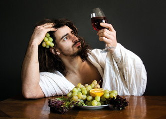 photo half naked curly guy sitting at the table with fruits looks at a glass of wine