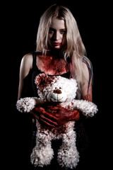 Bloody young woman holding a teddy bear