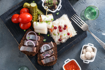 Vodka with various traditional snacks and appetizers: pickled cabbage, cucumber, tomato, herring, lard, potato, sauce