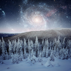 Fantastic starry sky. Beautiful winter landscape and snow-capped