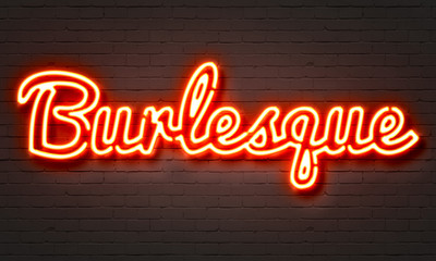 Burlesque neon sign on brick wall background.
