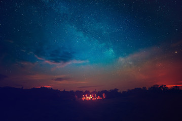 Camping fire under the amazing blue starry sky with a lot of shining stars and clouds. Travel recreational outdoor activity concept. Fototapete