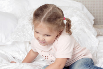 Little girl has fun in a bed. Portrait of child in the bedroom.