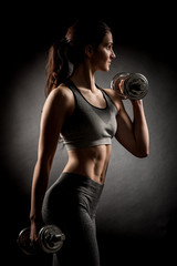 Atractive fit woman works out with dumbbells as a fitness conceptual over dark background