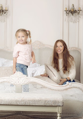Mother plays with her little daughter. Woman and child are having fun on the bed.