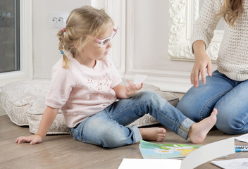 The daughter and mother sit on the floor and draw. The woman helps to the child to draw with markers.