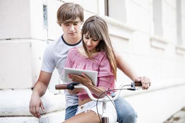 Young couple on bicycle, using digital tablet, Osijek, Croatia