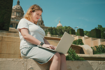 Plus size beautiful model girl working on her laptop while sitting on stairs in sunny day, young woman in white t-shirt and grey skirt is having online chat with her business colleagues using net-book