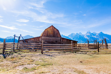 Grand Teton National Park, Jackson Hole, Wyoming.  Barn in a grass field plain against the Grand Teton mountain range with the sun shining